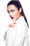 Προκλητικό μοντέρνο πρότυπο μόδας στο άσπρο παλτό με τα κόκκινα χείλια Στοκ Φωτογραφίες