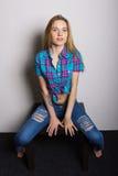 Προκλητικό νέο κορίτσι στα τζιν και ένα πουκάμισο καρό που θέτει τη συνεδρίαση στο τραπεζάκι σαλονιού Στοκ φωτογραφίες με δικαίωμα ελεύθερης χρήσης