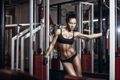Προκλητικό νέο κορίτσι στην εκμετάλλευση γυμναστικής στη μηχανή κατάρτισης Στοκ Εικόνα