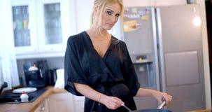 Προκλητικό ξανθό μαγειρεύοντας γεύμα νοικοκυρών απόθεμα βίντεο