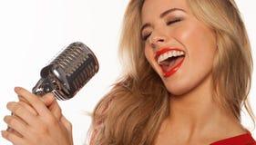 Προκλητικό ξανθό τραγούδι τραγουδιστών στοκ εικόνα