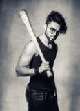 Προκλητικό πρότυπο ατόμων μόδας με ένα ρόπαλο του μπέιζμπολ που φαίνεται ενάντια στον τοίχο grunge Στοκ εικόνες με δικαίωμα ελεύθερης χρήσης