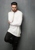 Προκλητικό πρότυπο ατόμων μόδας στην άσπρη τοποθέτηση πουλόβερ, τζιν και μποτών δραματική στοκ εικόνα