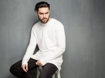 Προκλητικό πρότυπο ατόμων μόδας στην άσπρη τοποθέτηση πουλόβερ, τζιν και μποτών δραματική στοκ εικόνες