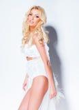 προκλητικό πρότυπο γυναικών που ντύνεται στην άσπρη τοποθέτηση ενάντια στον τοίχο Στοκ εικόνες με δικαίωμα ελεύθερης χρήσης