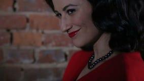 Προκλητικό Brunette στο κόκκινο φλερτ φορεμάτων, που χορεύει και απόθεμα βίντεο