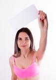 Προκλητικό brunette fitnes σε μια φόρμα γυμναστικής που κρατά τον κενό λευκό πίνακα Στοκ Εικόνες