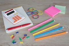 Προμήθειες γραφείων, επιχειρησιακά εξαρτήματα με τα μολύβια χρώματος και σημειωματάριο στον ξύλινο πίνακα Στοκ φωτογραφίες με δικαίωμα ελεύθερης χρήσης