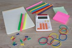 Προμήθειες γραφείων, επιχειρησιακά εξαρτήματα με τα μολύβια χρώματος και σημειωματάριο στον πίνακα Στοκ Φωτογραφία