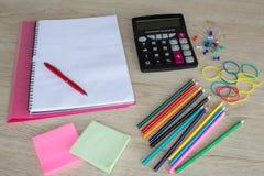 Προμήθειες γραφείων, επιχειρησιακά εξαρτήματα με τα μολύβια χρώματος και σημειωματάριο στον ξύλινο πίνακα Στοκ εικόνες με δικαίωμα ελεύθερης χρήσης