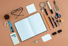 Προμήθειες γραφείων που οργανώνονται τακτοποιημένα γύρω από το σημειωματάριο Στοκ Φωτογραφία