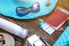 Προμήθειες διακοπών ταξιδιού: καπέλο, γυαλιά ηλίου, πτώσεις κτυπήματος, διαβατήριο καμερών και εισιτήρια αερογραμμών στο παλαιό ξ στοκ φωτογραφία
