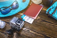 Προμήθειες διακοπών ταξιδιού: καπέλο, γυαλιά ηλίου, πτώσεις κτυπήματος, διαβατήριο καμερών και εισιτήρια αερογραμμών στο παλαιό ξ στοκ φωτογραφίες