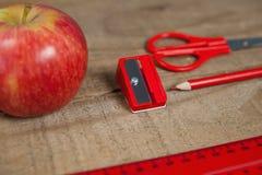 Προμήθειες της Apple και σχολείων στον ξύλινο πίνακα Στοκ Εικόνα