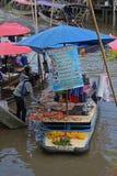 Προμηθευτής που πωλεί τα ψημένα στη σχάρα φρέσκα θαλασσινά σε μια να επιπλεύσει αγορά στη Μπανγκόκ Ταϊλάνδη Στοκ εικόνα με δικαίωμα ελεύθερης χρήσης