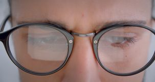 Προοδευτικό καυκάσιο freelancer eyeglasses με τις εργασίες ponytail με τη ηλεκτρονική συσκευή που είναι προσεκτική φιλμ μικρού μήκους