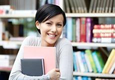 Προπτυχιακός φοιτητής με βιβλίο στη βιβλιοθήκη στοκ εικόνες