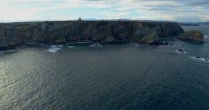 Προς τα κάτω μετακίνηση κατά μια γενική εναέρια άποψη κοντά στη θάλασσα που φτάνει πιό κοντά στην ακτή με πολλούς απότομους βράχο απόθεμα βίντεο