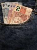 προσέγγιση στην μπροστινή τσέπη των τζιν στο μπλε με τα βραζιλιάνα τραπεζογραμμάτια στοκ εικόνες