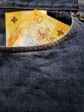 προσέγγιση στην μπροστινή τσέπη των τζιν στο μπλε με τα ελβετικά τραπεζογραμμάτια στοκ εικόνες