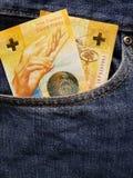 προσέγγιση στην μπροστινή τσέπη των τζιν στο μπλε με τα ελβετικά τραπεζογραμμάτια στοκ εικόνα με δικαίωμα ελεύθερης χρήσης