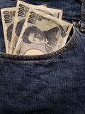 προσέγγιση στην μπροστινή τσέπη των τζιν στο μπλε με τα ιαπωνικά τραπεζογραμμάτια στοκ εικόνα