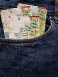 προσέγγιση στην μπροστινή τσέπη των τζιν στο μπλε με τα ισραηλινά τραπεζογραμμάτια στοκ φωτογραφίες