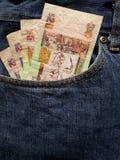 προσέγγιση στην μπροστινή τσέπη των τζιν στο μπλε με τα μπελιζινά τραπεζογραμμάτια στοκ εικόνα