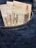 προσέγγιση στην μπροστινή τσέπη των τζιν στο μπλε με τα τραπεζογραμμάτια Ουρουγουανών στοκ φωτογραφία