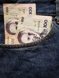 προσέγγιση στην μπροστινή τσέπη των τζιν στο μπλε με τα τραπεζογραμμάτια Ουρουγουανών στοκ εικόνες