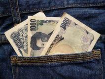 προσέγγιση στην πίσω τσέπη των τζιν στο μπλε με τα ιαπωνικά τραπεζογραμμάτια στοκ εικόνες