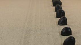 Προσέγγιση των μαύρων πετρών που στέκονται σε ανοικτή επικοινωνία από την άμμο μετακινηθείτε απόθεμα βίντεο