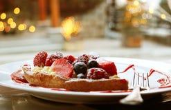 Προσέχοντας μέσω του παραθύρου πέρα από το κέικ φρούτων με τα μούρα και το δίκρανο, έτοιμα ναφαγωθούν Στοκ Φωτογραφίες