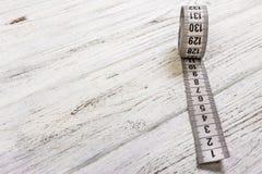 Προσαρμογή της άσπρης μετρώντας ταινίας μετρητών στο ξύλινο υπόβαθρο Στοκ Εικόνα