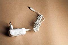 Προσαρμοστής εναλλασσόμενου ρεύματος lap-top σε καφετί χαρτί τεχνών Στοκ Εικόνες