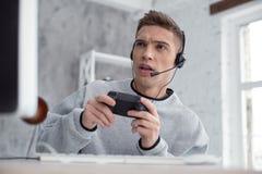 Προσεκτικά παίζοντας παιχνίδια στον υπολογιστή νεαρών άνδρων Στοκ Φωτογραφίες