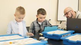 Προσεκτικές αρσενικές βοήθειες δασκάλων στους νέους σπουδαστές του για να πάρει πώς ο ψηφιακός προγραμματισμός λειτουργεί σε αργή απόθεμα βίντεο