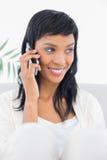 Προσεκτική μαύρη μαλλιαρή γυναίκα στα άσπρα ενδύματα που καλούν κάποιο με το κινητό τηλέφωνό της Στοκ εικόνες με δικαίωμα ελεύθερης χρήσης