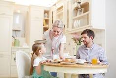 Προσεκτική μητέρα που βάζει το πιάτο με τις τηγανίτες στοκ εικόνα