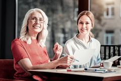 Προσεκτικοί εύθυμοι συνάδελφοι που χαμογελούν υπογράφοντας τα έγγραφα Στοκ εικόνες με δικαίωμα ελεύθερης χρήσης