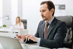 Προσεκτικός ανώτερος υπάλληλος που ελέγχει τα σημαντικά έγγραφα στο γραφείο Στοκ εικόνες με δικαίωμα ελεύθερης χρήσης