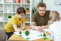 Προσεκτικός εμπνευσμένος γενειοφόρος δάσκαλος που βοηθά τους μαθητές του με τη χειροποίητη αφίσα στοκ εικόνες