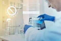 Προσεκτικός επιστήμονας που χύνει το μπλε υγρό στους σωλήνες δοκιμής ενώ όντας σε ένα εργαστήριο Στοκ φωτογραφία με δικαίωμα ελεύθερης χρήσης