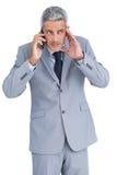 Προσεκτικός επιχειρηματίας που απαντά στο τηλέφωνο Στοκ Εικόνα