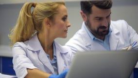 Προσεκτικός θηλυκός ερευνητής που βοηθά το συνάδελφο με το πείραμα απόθεμα βίντεο