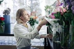 Προσεκτικός νεαρός άνδρας που παίρνει τα λουλούδια από το βάζο στοκ φωτογραφία με δικαίωμα ελεύθερης χρήσης
