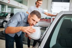Προσεκτικός στις λεπτομέρειες ο πελάτης κλίνει στο άσπρο αυτοκίνητο και την αγγίζει Ο νεαρός άνδρας κοιτάζει στον καθρέφτη Είναι  στοκ εικόνες