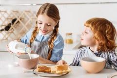 Προσεκτικό λατρευτό κορίτσι που προσθέτει το γάλα στα δημητριακά της Στοκ Εικόνα