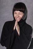 Προσευμένος γυναίκα στο μαύρο φόρεμα με την κουκούλα σε ένα γκρίζο υπόβαθρο Στοκ φωτογραφίες με δικαίωμα ελεύθερης χρήσης