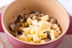 Προσθέστε τις πατάτες στα λαχανικά στο τηγάνι Στοκ εικόνα με δικαίωμα ελεύθερης χρήσης